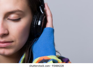Girl listening to music against grey background