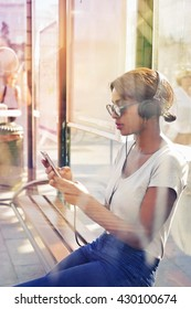 Girl listening to music at the bus stop
