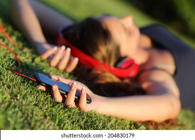 Girl listening music with headphones and holding a smart phone lying on the green grass in a park