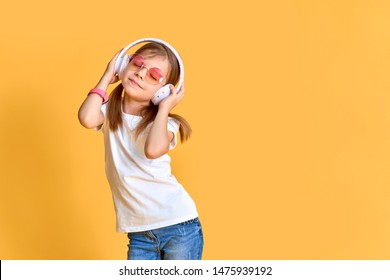 Girl listening to music in headphones on yellow background. Cute child in colored sunglasses enjoying happy dance music, smile, posing on pink studio background wall.
