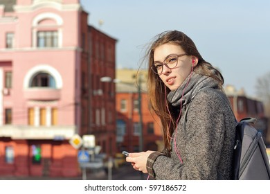 Girl listening to music on headphones while walking around the city. She has a good mood and she smiles. A student is wearing a coat and a scarf around her neck, the girl is wearing glasses.