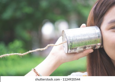 a girl listening through the tin can telephone, communication concept like a Telegram. The old days toy.