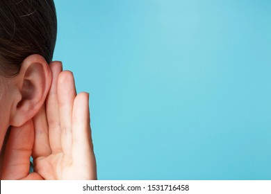 The girl listens attentively with her palm to her ear close up, the news concept