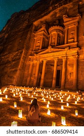 A girl listens to a Bedouine singer in front of the treasury of Petra by night in the desert of Jordan. Petra is one of the New 7 Wonders of the World and a UNESCO world heritage site.