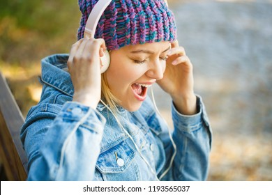 Girl listens to music in headphones. Smiling girl relaxing, music a smartphone and headphones. Outdoors portrait of a trendy girl. Autumn melody concept. Fall cozy atmosphere. Woman with big headphone