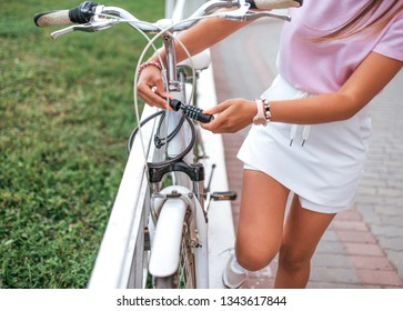 A girl locks her bike in the summer in the city, a curb fence, a lock on the frame of the bike, password selection with a cipher code. Protection against theft and theft of parked vehicles.