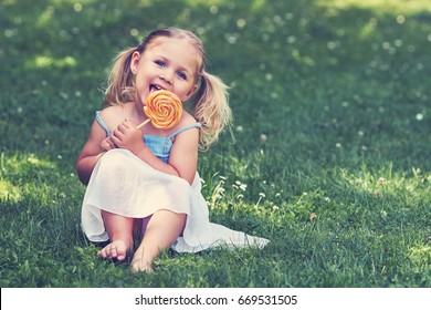 Girl with lollipop / Young girl with lollipop sitting on a meadow