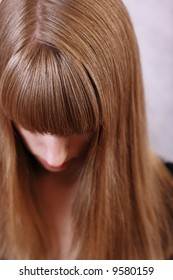 a girl with long blond beautiful lock of hair hanging down