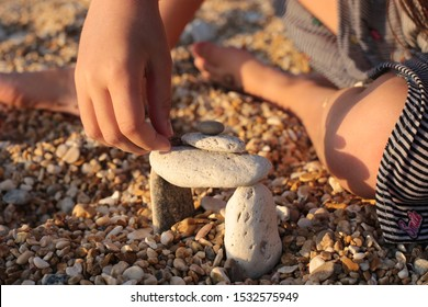A girl and long blond hair on the seashore plays in stones builds a tower of stones