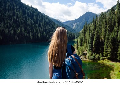 Girl with long blonde hair and backpack is looking at the Lower Kolsay Lake and mountains. Tian Shan Mountains in Kazakhstan