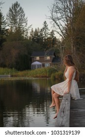 Girl with long brown hair sitting on dock watching the sunset.