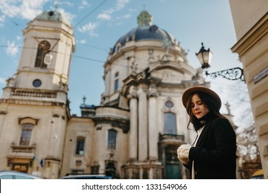 Girl with a long brown hair wearing a hat. Woman lifestyle portrait with an old gorgeous church on the background. City architecture and people. Checking out city landscape