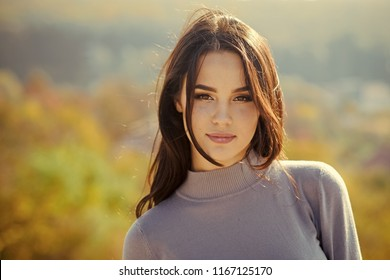 Girl with long brunette hair enjoy autumn nature. Woman face with makeup on sunny day. Skincare, youth, health. Cosmetics, visage, make up. Fashion, beauty concept.