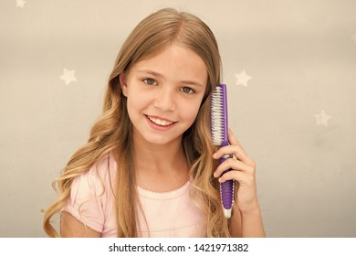 Girl long curly hair grey interior background. Child curly hairstyle hold hairbrush or comb. Apply oil before combing hair. Healthy hair. Conditioner or mask organic oil comb hair. Beauty salon tips.