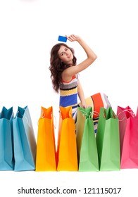 A girl in a long dress color, sitting next to a shopping bag with a credit card on a white background.