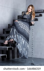 girl in a long dress sitting on stairs