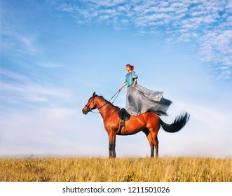 girl in a long dress standing on a horse in the field