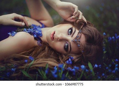 girl with long hair and blue eyes in the tiara rests in spring forest blue forest flowers. Girl Princess dreams.