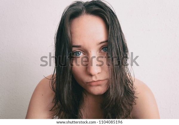a girl with long hair and blue eyes looking at camera