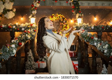 A girl with long hair in Christmas decorations. A girl in a beige coat stands in profile and catches snowflakes with her palms.