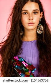 A girl with long hair and colorful big earrings.