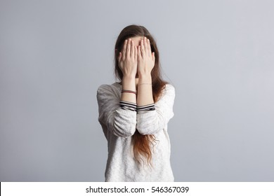Girl with long hair covers his face with his hands. Depression and loneliness in youth.