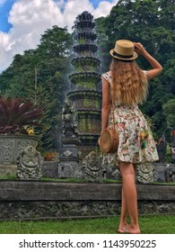 A girl with long hair in a dress with flowers in a straw slap and with a straw round bag looks up at the tower-fountain in the palace of Tirta Gangga in the Bali island