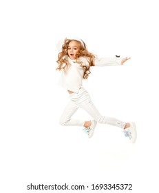 girl with long hair, dressed in white colored clothes, is jumping on a white background.