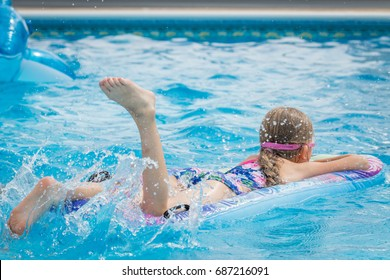 Girl with long hair enjoying the swimming pool in the Summer, kicking the water, lying on a inflatable mattress