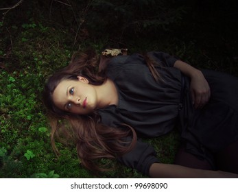 girl with long hair lying in the grass in the forest