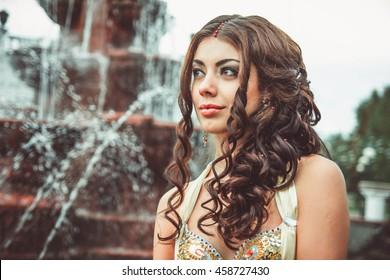 girl with long hair near the fountain.Beautiful woman standing near the fountain.
