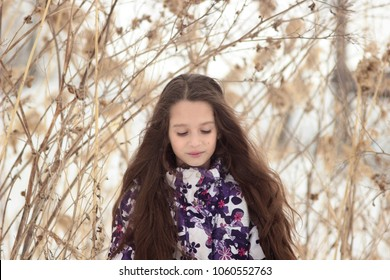 girl with long hair on background of a winter field