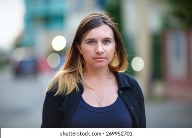 Girl with long hair on a background blur bokeh. Woman looking into the camera. Shallow depth of field. Focus on the model's face.