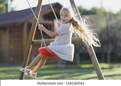 A girl with long hair on a swing on a playground in the courtyard of the house