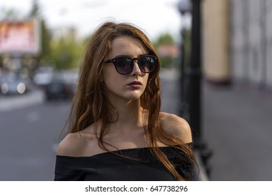 Girl with long hair posing on city street