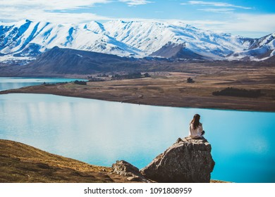 Girl with long hair sit on a rock looking at Lake Tekapo