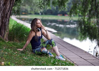 The girl with long hair sits ashore and looks in a distance.