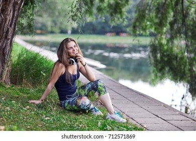 The girl with long hair sits ashore and looks in the camera.