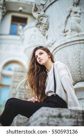 The girl with long hair sits beside a beautiful building with columns and stucco