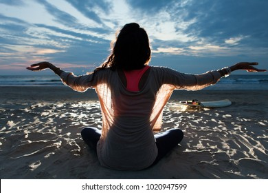 Girl with long hair sitting on the beach in lotus pose embracing last sunset light with open arms