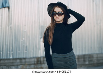girl with long hair and skirt stands near a high wall