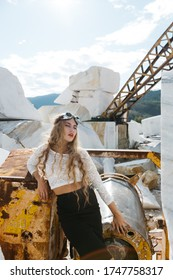 A girl with long hair in special glasses posing on special equipment at a marble quarry