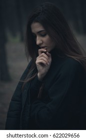 A girl with long hair is standing in the wood in dark clothes. Low key