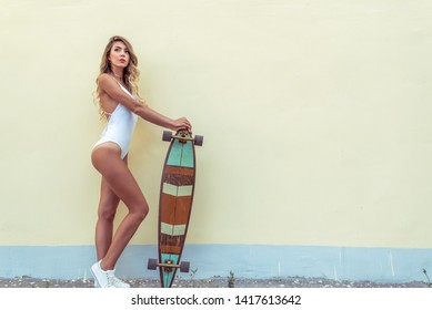 Girl with long hair years city, rest with board. Concept fashion style modern lifestyle young people. Free space text. Tanned fitness workout figure. Background homogeneous flat yellow wall