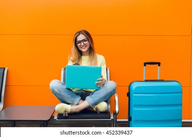 Girl with long hair in yellow sweater is sitting on orange background. She has blue suitcase and laptop. She is smiling happy.