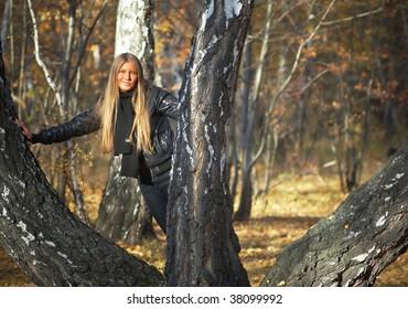 Girl with long hear near autumn trees