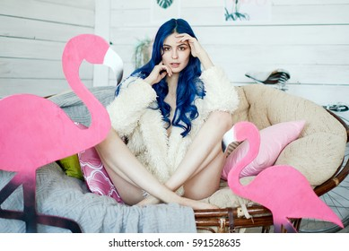 girl with long legs and blue hair in a fur jacket posing in a chair with a pink flamingo in a vintage studio