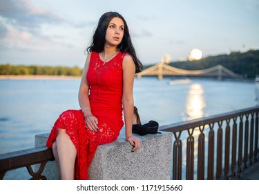 A girl in a long red dress is sitting on the fence of the river embankment.