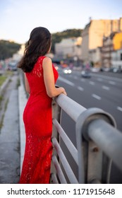 Girl in a long red dress is standing near the fence of the roadway.