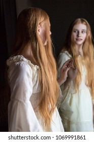 girl with long red hair looking into mirror